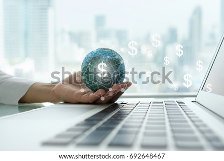 digital economy and income online concept. global on hand with network revenue dollar money icon and laptop computer. ストックフォト ©
