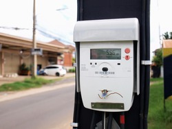 Digital electricity meter on the pole. A new high-precision electric current technology On the background of paved roads and houses. Selective focus