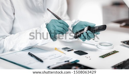 Digital Forensic Science. Police Forensic Analyst Examining Confiscated Mobile Phone. Stock photo ©
