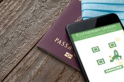 Digital Green Pass concept: Smartphone over a passport and a surgical mask on a wooden table show an hypotetical app for the Digital Green Passport (or digital pass certificate)
