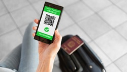Digital Health Passport app for smartphone with vaccinated sign and quad code. Woman leaving with passport and baggage. Coronavirus concept.