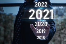 Digital infographic celebration 2021 year concept. Businessman pointing in the air with a virtual screen and popup 2021 text.