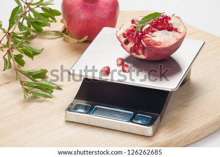 Digital kitchen scale on table and pomegranate.