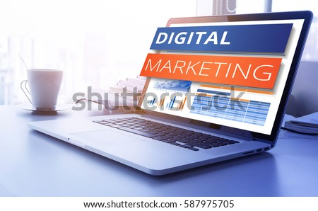 Digital marketing text on modern laptop screen with graph chart background. business marketing, success and goals concept