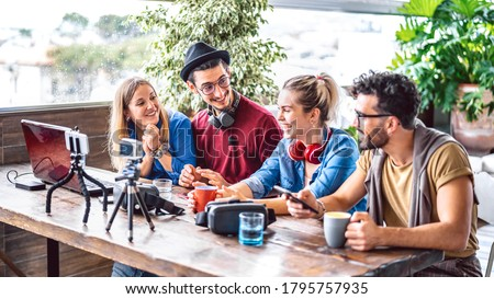 Digital native friends sharing feed on streaming platform with phone and web cam - Content marketing concept with millenial workers having fun vlogging live video on social media space - Bright filter Stok fotoğraf ©