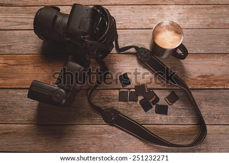 Digital photo camera, memory cards and cup of coffee on wooden table