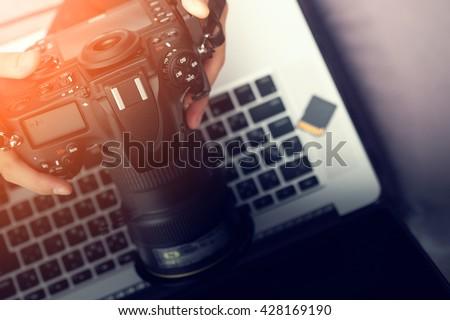 Digital Photography Workstation. Modern Digital DSLR Camera, Laptop Computer and Display.