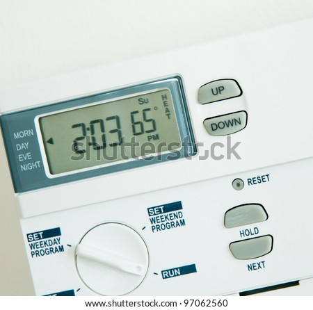 Digital programmable Thermostat at 65 degree heat isolated on White background