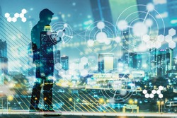 Digital revolution and Internet of Things concept. Double exposure of night city light and silhouette of business man standing and using smart phone with futuristic connection icons.