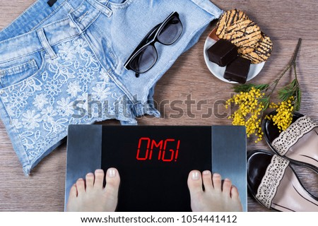 Digital scales with female feet and sign omg! surrounded by mimosa flowers, shorts and sweets. Effect of unhealthy food at body. Concept of being in form before spring and summer. Top view. Flat lay.
