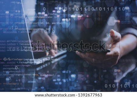 Digital software development, Internet technology concept. Software apps developer, man programmer working on mobile phone and laptop with binary, javascript computer code, big data on virtual screen