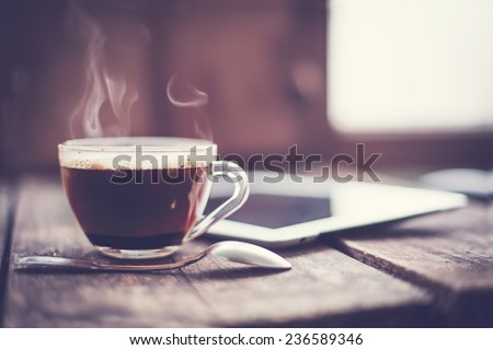 Stock Photo Digital tablet and cup of coffee on old wooden desk. Simple workspace or coffee break in morning/ selective focus