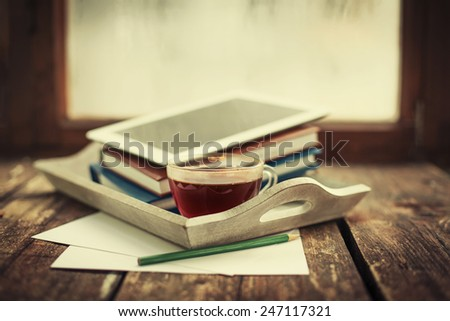 Digital tablet and cup of coffee on old wooden desk. Simple workspace or coffee break in morning/