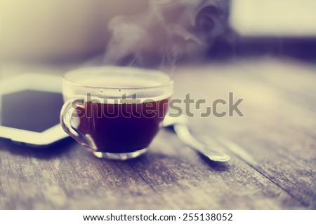 Digital tablet and cup of coffee on old wooden desk. Simple workspace or coffee break in morning/ selective focus #255138052