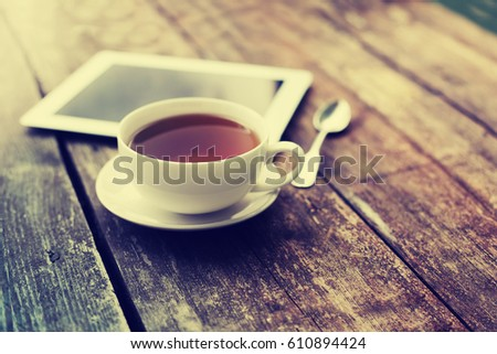 Digital tablet and cup of coffee on old wooden desk. Simple workspace or coffee break in morning/ selective focus  #610894424