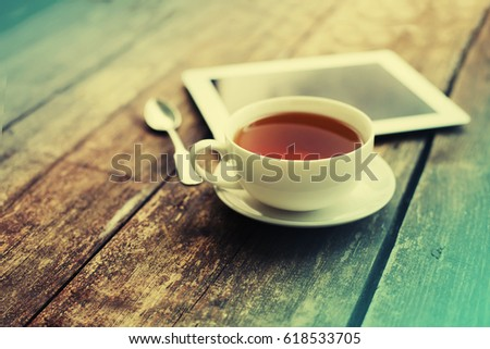 Digital tablet and cup of coffee on old wooden desk. Simple workspace or coffee break in morning/ selective focus #618533705