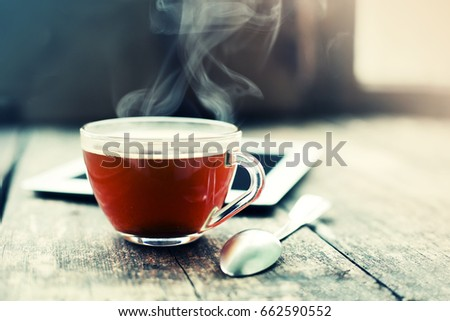 Digital tablet and cup of coffee on old wooden desk. Simple workspace or coffee break in morning/ #662590552