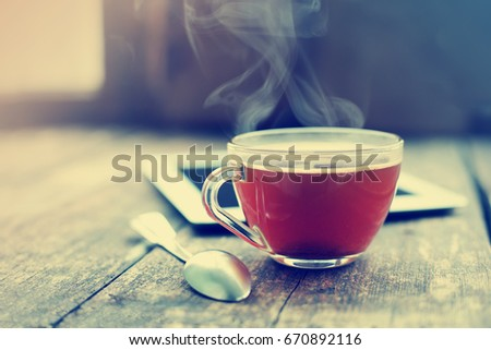 Digital tablet and cup of coffee on old wooden desk. Simple workspace or coffee break in morning/ #670892116