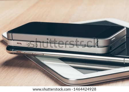 Digital tablet and mobile phone. Electronic devices on wooden table, close up. #1464424928