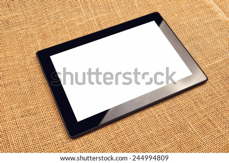 Digital Tablet Computer with Blank White Screen as Copy Space on Office Desktop.