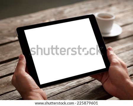 Digital tablet computer with isolated screen in male hands over cafe background - table, cup of coffee...