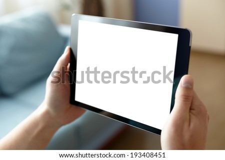 Digital tablet computer with isolated screen in male hands over home or office background - Shutterstock ID 193408451