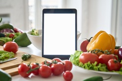 Digital tablet computer with mockup white screen on vegetarian healthy food vegetable background. Online grocery shopping delivery app ads concept, cook book diet plan nutrition recipes, close up view