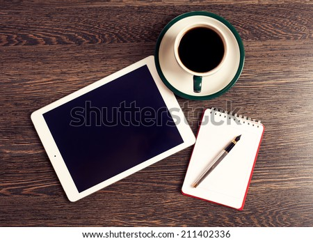 Digital tablet computer with note paper and cup of coffee on old wooden desk. Simple workspace or coffee break with web surfing.