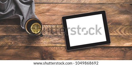 Digital tablet Ipad and a tea cup on wooden table. Flat lay.