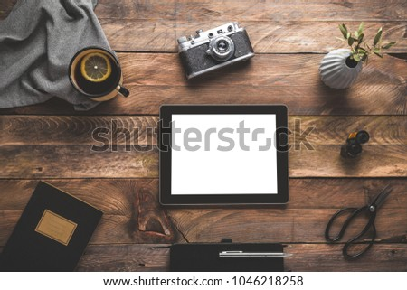 Digital tablet Ipad, camera, tea cup and a plant on wooden table. Flat lay.