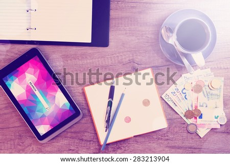 Digital tablet, sticky note paper, cup of coffee and money on old wooden desk. Simple workspace or coffee break with web surfing.