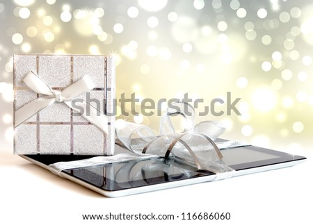 Digital tablet with christmas present on defocused lights