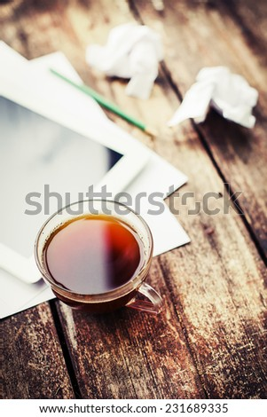 Digital tablet with note paper and cup of tea on old wooden desk. Simple workspace or coffee break in morning/ selective focus