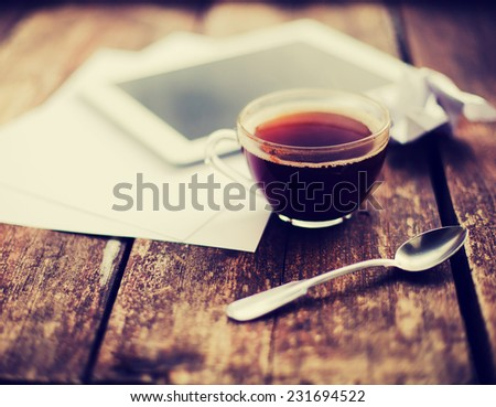Digital tablet with note paper and cup of tea on old wooden desk. Simple workspace or coffee break in morning/ selective focus  #231694522