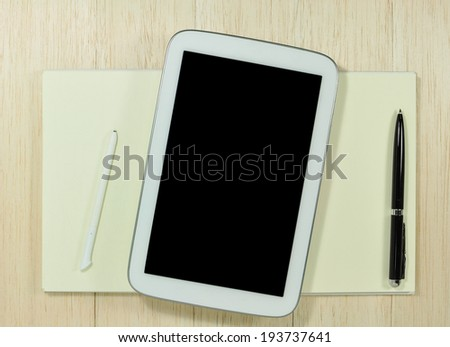 digital tablet with notepad and pen on wooden tablet.