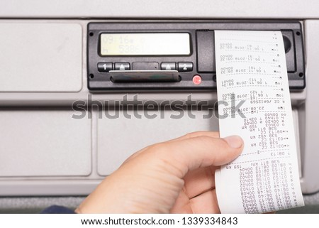 Digital tachograph and drivers hand holding print with driving times of the day. No personal data