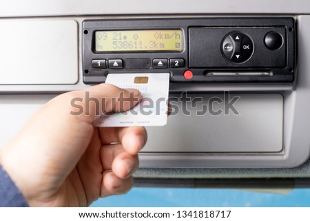 Digital tachograph and drivers hand inserting drivers card in it.