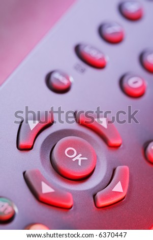 Digital television remote control buttons in red light.