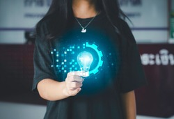 Digital transformation concept. Hand holding light bulb modern interface futuristic blue gear digital and binary coded background. Connection next generation technology and new era of innovation.