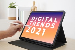 Digital Trends 2021 on tablet screen with hand holding interactive pen, Digital marketing, Business and technology concept.
