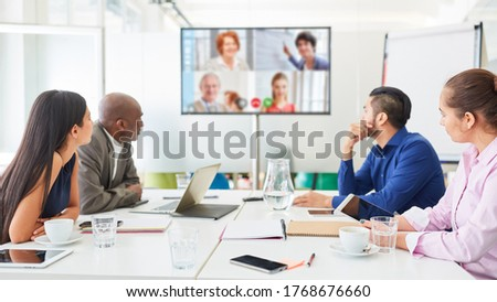 Digital video conference on monitor at business team meeting in conference room