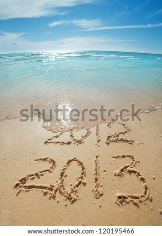digits  2012 and 2013 on the sand seashore - concept of new year