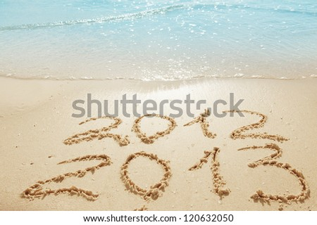 digits  2012 and 2013 on the sand seashore - concept of new year and passing of time