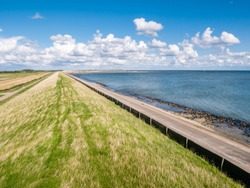 Dike with grass protecting polders on West Frisian island Texel against Wadden Sea, Netherlands