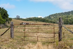 Dilapidated and abandoned old house and shed locked behind a rusted gate, a dairy farm ruined by the economic downturn