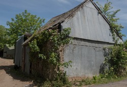 Dilapidated Corrugated Metal Barn in a Farmyard on a Farm in Rural Devon, England, UK
