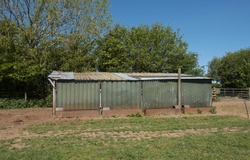 Dilapidated Corrugated Metal Livestock Shelter in a Paddock on a Farm in Rural Devon, England, UK