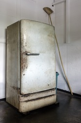 Dilapidated, dirty and rusty vintage refrigerator