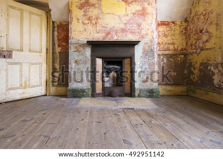 Dilapidated interior of historic English fort fireplace and worn wooden floor #492951142