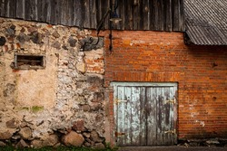Dilapidated old stone and red brick facade of an abandoned ancient building with blue weathered door.